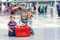 在机场照顾和两个小兄弟姐妹男孩 库存照片