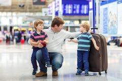 在机场生和两个小兄弟姐妹男孩 库存图片