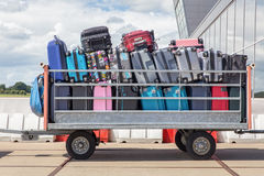 在机场的拖车充满手提箱 免版税库存图片