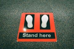 在机场站立这里标志在安全检查站 免版税库存图片