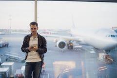 在机场终端里面的旅客 使用手机的年轻人和等待他的飞行 免版税库存照片