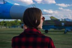在机场观看的飞机的少妇等待的飞行在日出或日落 库存图片