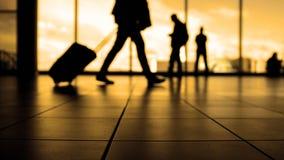 在机场走到离开的旅行家由在窗口,剪影前面的自动扶梯,温暖 库存照片