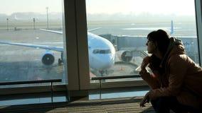 在机场,在候诊室,在俯视飞机和跑道的窗口的背景中,年轻人 股票视频