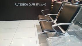 在机场终端的空位用咖啡邀请 免版税库存照片