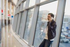 在机场终端里面的旅客 使用手机的年轻人和等待他的飞行 库存照片