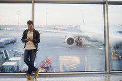 在机场终端里面的旅客 使用手机的年轻人和等待他的飞行 免版税库存图片