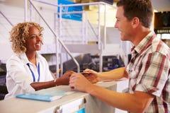 在机场登记书桌递到乘客的职员票 图库摄影