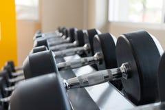 在机架关闭的黑哑铃集合在体育健身俱乐部重量训练器材概念 库存照片