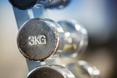 在机架的老镀铬物3kg哑铃 免版税库存照片