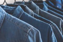 在机架的许多各种各样的牛仔布夹克 免版税库存图片