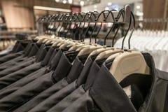 在机架的黑和蓝色衬衣吊,人在挂衣架的` s衬衣在衣橱 免版税图库摄影