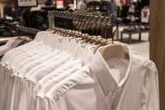 在机架的黑和蓝色衬衣吊,人在挂衣架的` s衬衣在衣橱 免版税库存图片