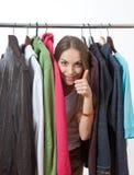 在机架附近的少妇有挂衣架的 免版税库存图片