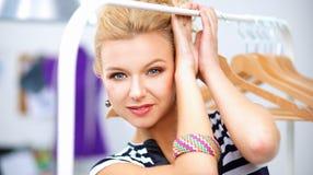 在机架附近的美丽的年轻美发师有挂衣架的在办公室 库存图片