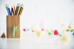 在杂乱书桌上的铅笔持有人 免版税库存图片