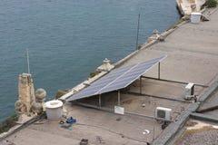 在杂乱屋顶的太阳电池板在水体的地中海区域旁边 免版税库存照片