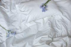 在杂乱床、白色卧具项目和蓝色花bouqet上的花 库存照片