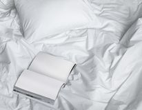 在杂乱床上的书,与书的创造性的照片构成和在太阳光下的白色床从窗口 库存图片