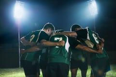 在杂乱的一团的橄榄球队在比赛以后 图库摄影