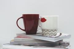在杂志堆顶部的咖啡杯 库存图片