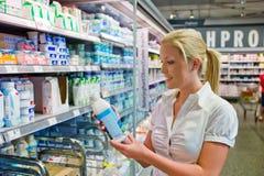 在杂货店的妇女买的牛奶 免版税库存照片