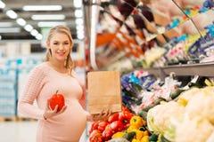 在杂货店的孕妇买的菜 库存照片