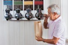 在杂货店的老人买的咖啡豆 免版税库存图片