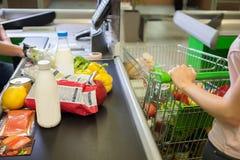 在杂货的少妇买的食物 免版税库存照片