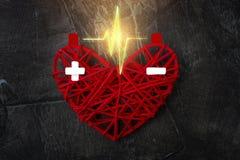 在杆之间的放电在红色心脏 充电加上和减 日愉快的s华伦泰 库存图片