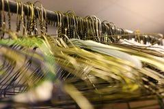 在杆的挂衣架在壁橱存贮的垂悬的衣物的 免版税库存图片