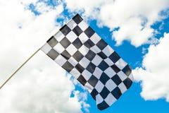 在杆的方格的旗子与在背景的云彩 免版税图库摄影