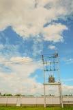 在杆的电导线,力量,与柔和的淡色彩的蓝天背景 库存照片
