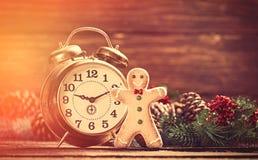 在杉木分支和姜饼附近的闹钟在木桌上 免版税库存图片