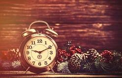 在杉木分支附近的闹钟在木桌上 图库摄影