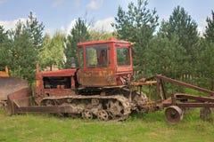 在杉木和冷杉木的老农用拖拉机在篱芭前 免版税库存照片