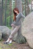 在杉木附近的大森林向妇女年轻人扔&# 免版税库存图片