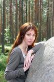 在杉木附近的大森林向妇女年轻人扔&# 库存图片