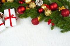 在杉树分支特写镜头、礼物、xmas球、锥体和其他对象在白色空白毛皮,假日概念的圣诞节装饰 免版税库存照片