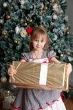 在杉树附近的小女孩与圣诞节礼物 微笑 免版税库存照片