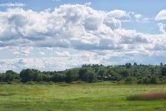在村庄上的多云天空绿色多小山谷的 免版税库存图片