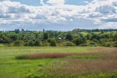 在村庄上的多云天空绿色多小山谷的 库存照片