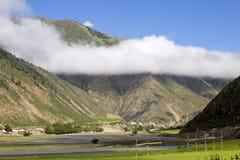 在村庄之下的山天空 库存照片