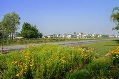 在村庄前的乡下路在晴朗的夏天早晨 免版税图库摄影