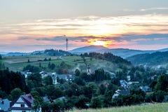 在村庄和青山的日落 免版税库存照片