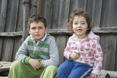 在村庄坐注册有男孩的春天女孩 免版税库存照片