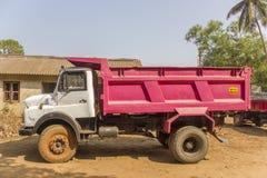 在村庄房子和绿色棕榈的背景的印度白色桃红色卡车 免版税库存图片