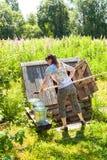在村庄木水井附近的年轻可爱的妇女总之 库存图片