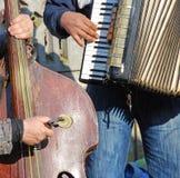 在村庄演奏低音提琴和手风琴的两位音乐家 图库摄影