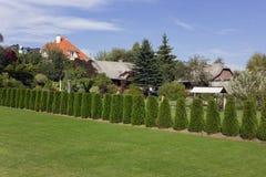 在村庄附近的理想的草草坪 库存照片